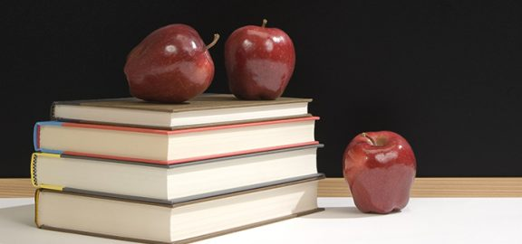 Four books stacked with three red apples