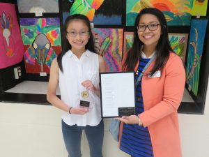 Oak Ridge Middle School's Elizabeth Low accepts an award from Janet Abejo of the City of Cedar Rapids' Civil Rights Commission for her award winning poem