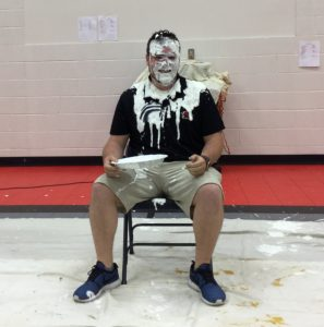 Mr. Phillips, Novak Elementary School Facilitator sitting in a chair after getting a pie to the face