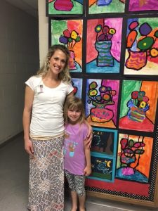 Wilkins Art Teacher Mrs. Hovden and a student pose in front of numerous pieces of student artwork