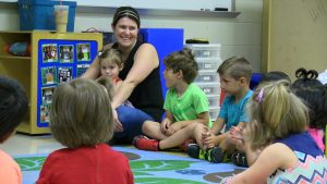 Parent Volunteer sits with students at storytime